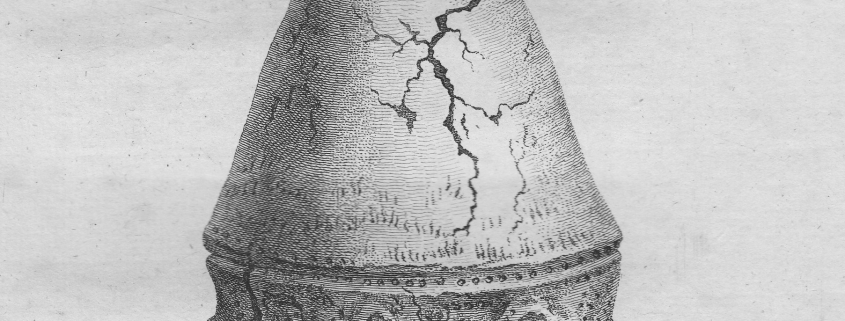 Grey scale image of upside down conical urn on a stone