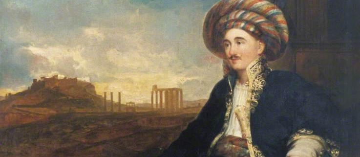 Oil painting of Robert Wilson wearing a Turkish costume, tucked into the waistband of this costume is a Persian dagger and sheath (ABDUA:63523). Scroll in left hand with list of Alexander's Conquests. Background shows the Ruins of Athens (?). Painted in Rome in 1824