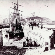 Black and white poor quality photo with sailing ships in foreground