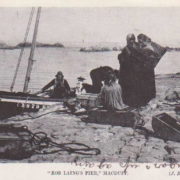 Grey scale postcard showing boat alongside Rob Laing's Pier, with various Lyall family members