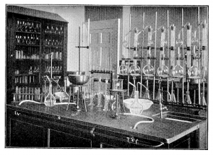 Black and white image showing old fashioned glass testing equipment, bunsen burners etc