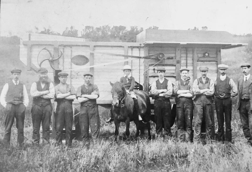 Wright Brothers and others in front of a threshing mill