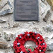 Colour photo of bronze plaque and wreath on a stone background